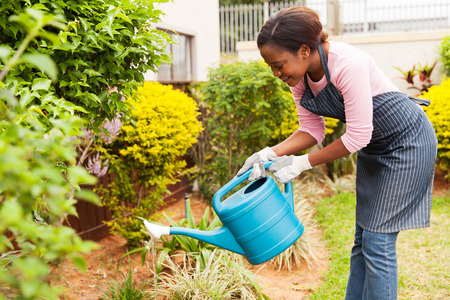 Feliz joven mujer africana que riega su jardín Foto de archivo - 49305561
