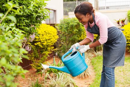 happy young african woman watering her garden Stockfoto