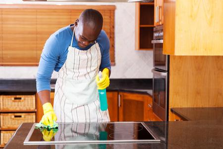 limpieza  del hogar: ocupada joven africano estufa de limpieza hombre en el hogar