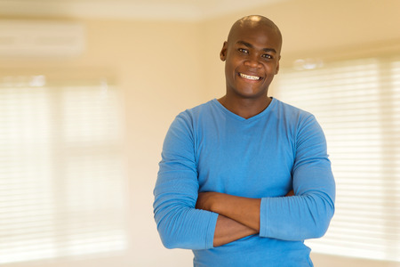 good looking: portrait of happy black man with arms folded
