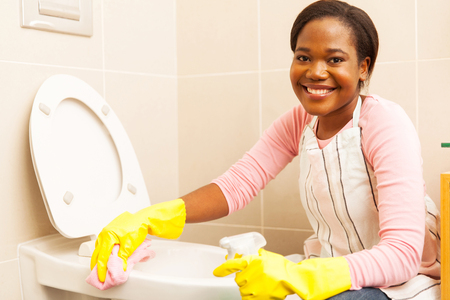 a toilet seat: pretty african woman cleaning toilet