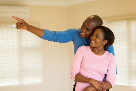 BLACK GIRL: cheerful young african couple looking round their new house Stock Photo