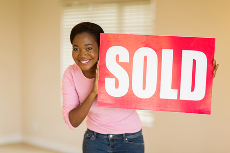 sold sign: joyful young african woman holding sold sign in her home