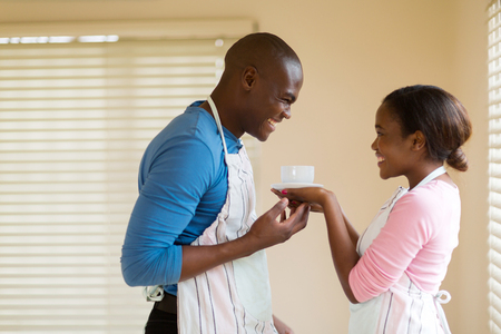 coffee houses: pretty african woman giving coffee to her husband at home