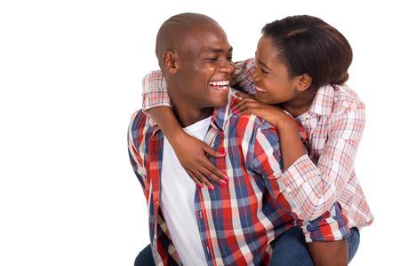 pareja abrazada: alegre joven pareja negro que lleva a cuestas sobre fondo blanco
