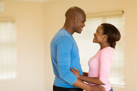 couple home: romantic african couple embracing in an empty house