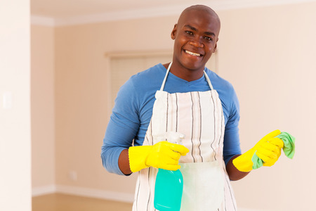 house cleaning: happy young african american man doing housework