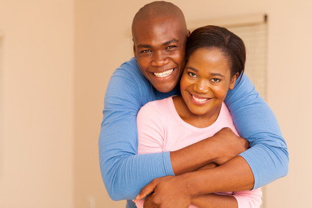 casados: portrait of handsome african american man hugging his wife