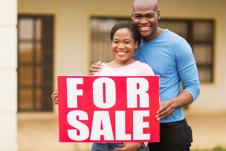 for sale sign: portrait of beautiful african american couple outside home with for sale sign