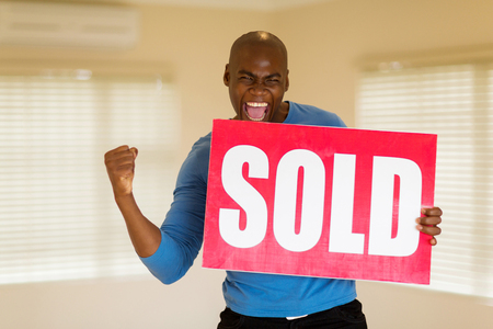 excited man: excited african man holding sold sign in his house Stock Photo
