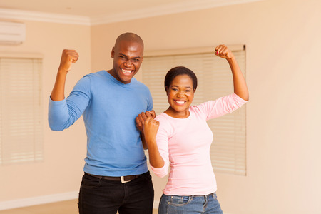 african dance: cheerful young african couple holding fist after buying a new apartment Stock Photo