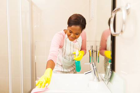 cleaning bathroom: african american woman cleaning bathroom sink at home Stock Photo