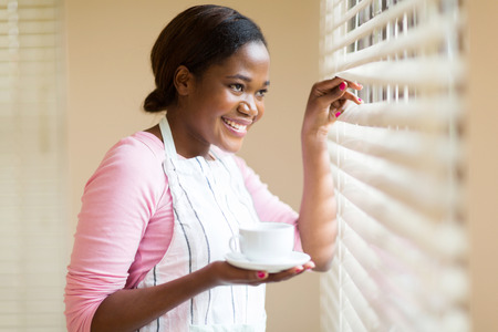 coffee house: happy african woman peeking through the blinds with coffee