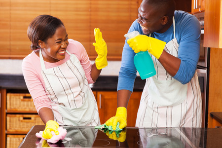 young african couple having fun while doing household chores Stock Photo