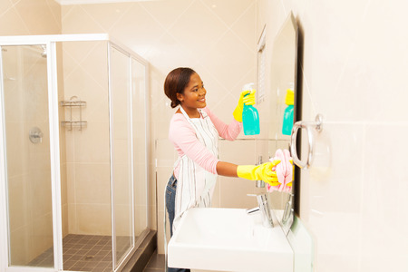 house cleaning: beautiful young african woman cleaning bathroom mirror