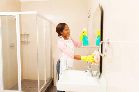 limpieza del hogar: joven y bella mujer africana ba�o de limpieza del espejo Foto de archivo