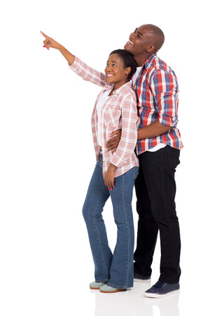 woman pointing up: cheerful young african american couple pointing at empty space