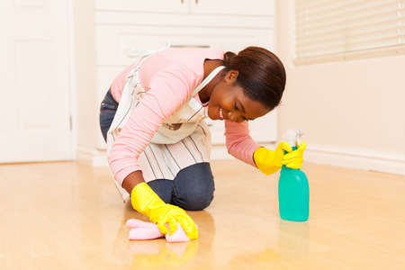 happy young african woman wiping wooden floor Stockfoto