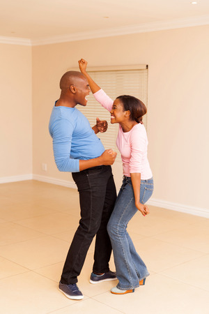 dancing house: excited black couple dancing at their new home Stock Photo