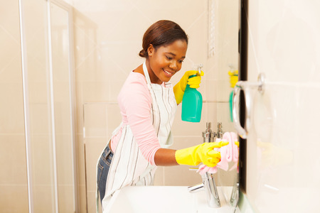 cleaning bathroom: smiling young woman cleaning bathroom mirror at home