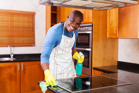 happy african: happy african american man cleaning stove