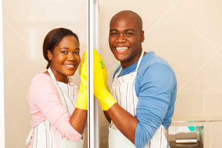 cleaning bathroom: portrait of afro american couple cleaning bathroom