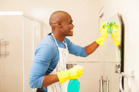 house cleaning: cheerful african man cleaning bathroom mirror at home