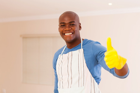 looking up: cheerful black man giving thumb up after doing housework