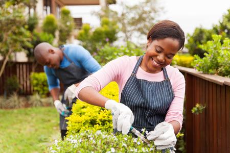 africano mulher jovem e atraente jardinagem com o marido em casa