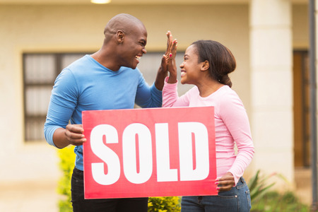 sold sign: cheerful young african couple holding sold sign and celebrating their house been sold