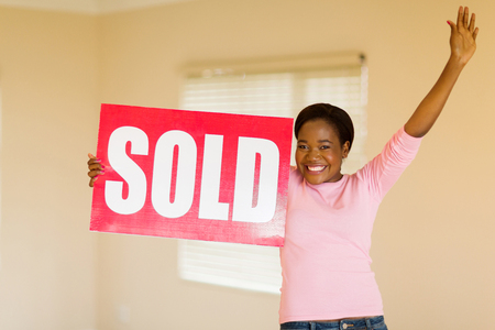 sold sign: excited young african american woman with sold sign indoors