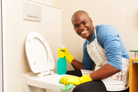 cleaning bathroom: portrait of happy african man cleaning toilet Stock Photo
