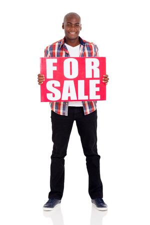 for sale sign: handsome african american man holding a for sale sign isolated on white Stock Photo