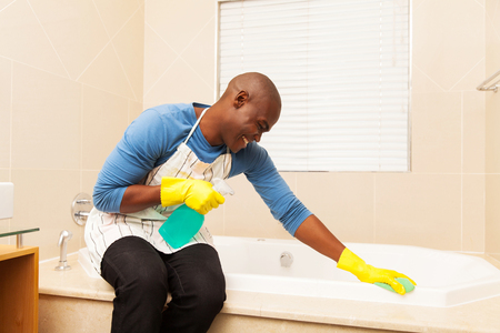 house cleaning: happy african american man cleaning up bathtub at home