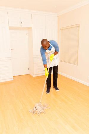 limpieza del hogar: hombre africano de fregar el suelo de su apartamento vac�o