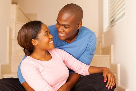 parejas enamoradas: joven pareja feliz africano sentado en el suelo en casa Foto de archivo