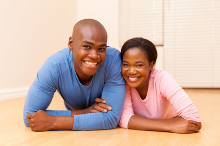 american house: happy young african couple lying on the floor