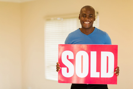 sold sign: happy young black man holding sold sign in his home