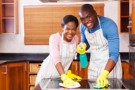 chores: young african american couple cleaning together in the kitchen Stock Photo