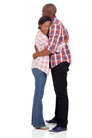 parejas romanticas: romantic african couple hugging with eyes closed on white background