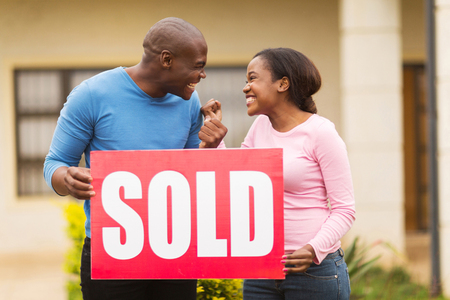 ethnicity: excited black couple holding sold sign outside their house