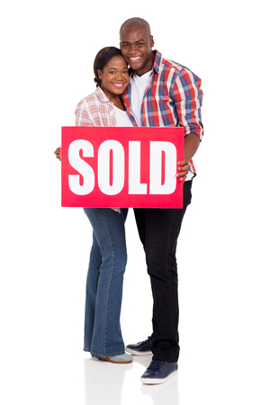 sold sign: portrait of lovely young african american couple holding a sold sign Stock Photo