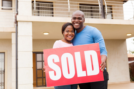 sold sign: portrait of young couple holding sold sign outside their house