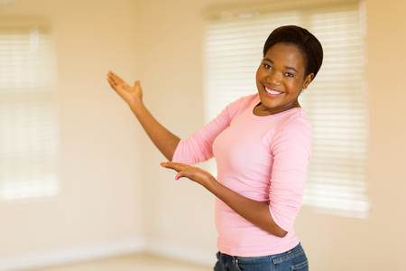 african american woman: happy african american woman doing welcoming gesture
