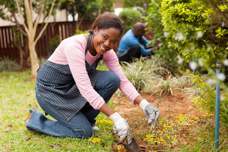 modern girls: beautiful african woman working in the garden with her husband