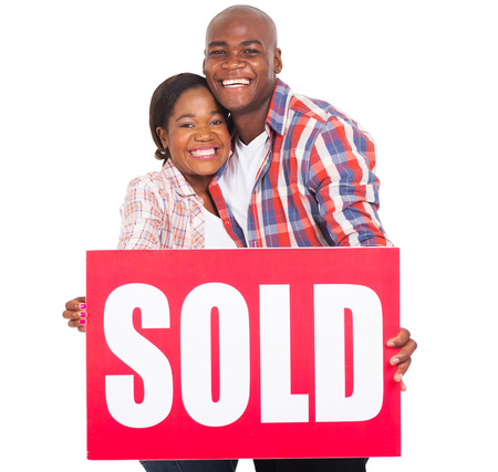 cheerful: cheerful african couple showing sold sign