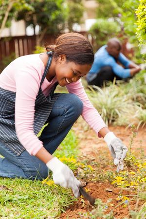 jardineros: bastante joven jardinería niña africana con su marido en el fondo