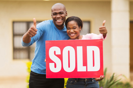 sold sign: happy african couple outside home with sold sign giving thumbs up