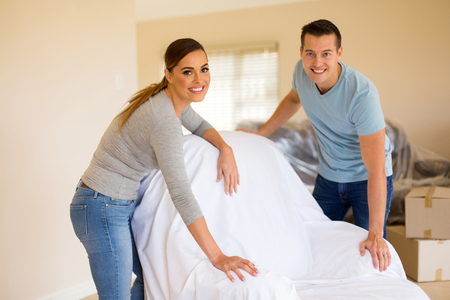 redecorating: portrait of couple cover furniture in new home Stock Photo