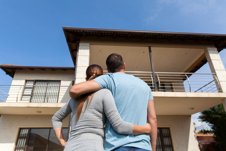 front view: rear view of young couple looking at their new house